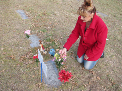 Cindy Chevalier visits the gravesite of her uncle, Council Bluffs Police Officer John Stephens